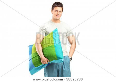 A smiling man in pajamas holding a pillow isolated on white background