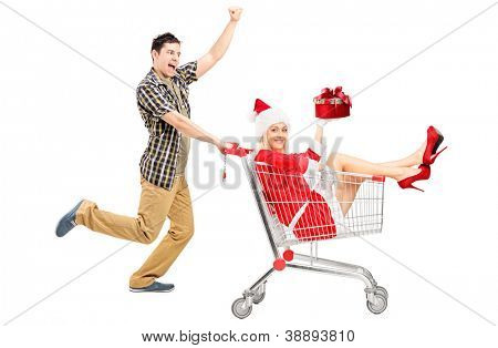 Excited man pushing a shopping cart and woman in christmas costume isolated on white background
