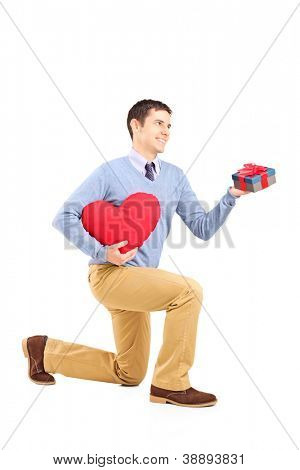 Male kneeling with gift and red  heart isolated on white background