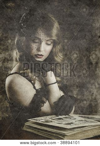woman looking in old photo album, vintage portrait on retro background