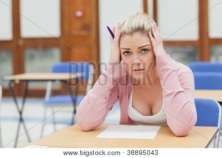 Woman looking worried over exam paper in exam hall in college