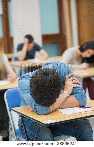 Boy sleeping at desk during exam in exam hall in college