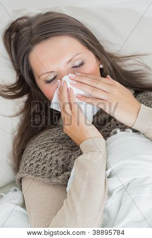 Woman lying on sofa and blowing nose in the living room