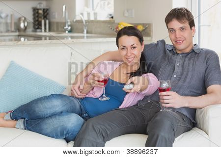 Young couple sitting on the couch and drinking wine while watching television