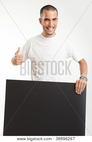 Young man holding a blackboard, with a happy expression