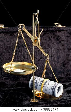 Weighing scales comparing wad of dollars and pile of white illegal drug
