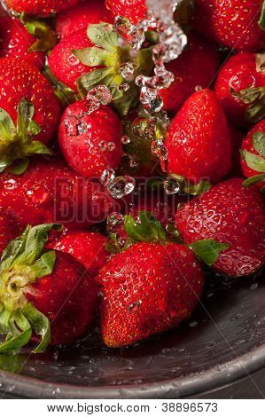 Macro shot on water falling on a group of strawberries