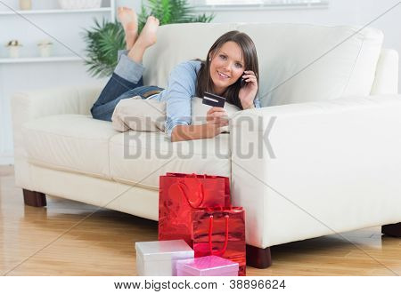 Woman lying on sofa holding a credit card and calling in the living room with shopping bags and presents on the floor