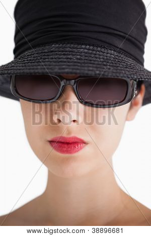 Woman wearing hat and sunglasses with red lips against white background