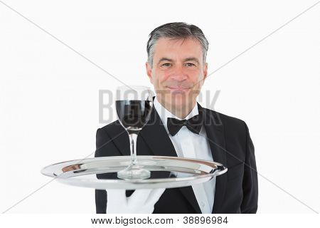 Smiling waiter holding a glass full of wine on a silver tray on white background