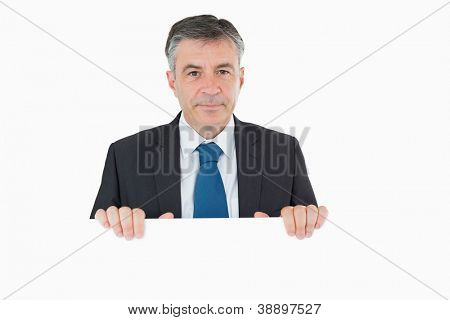 Thoughtful businessman standing behind white board