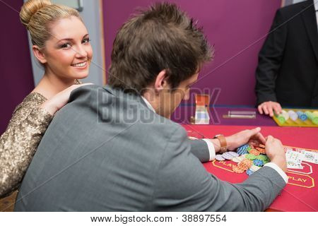 Woman smiling as man is taking winnings at poker game in casino