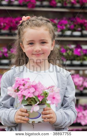 Little girl holding a plant while smiling in garden center