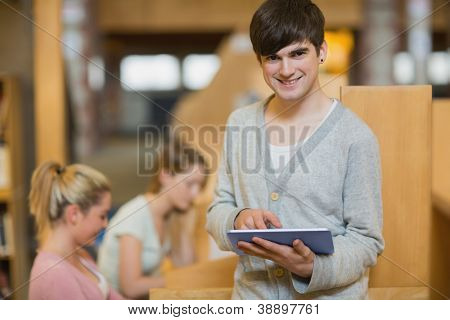 Man holding a tablet pc while standing at the college library smiling