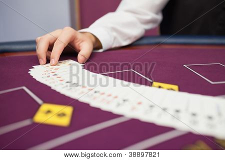 Dealer spreading the deck at poker game in casino