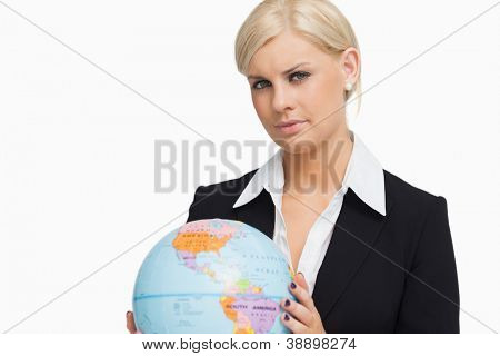 Serious blonde in suit holding a globe against white background