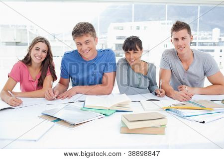 Four smiling students look up into the camera in a library