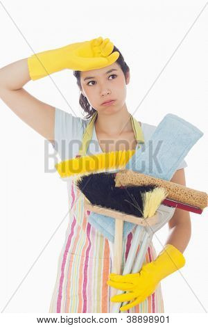 Overworked young woman holding cleaning tools