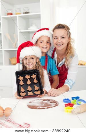 Kids wearing santa hats making christmas cookies with their mother
