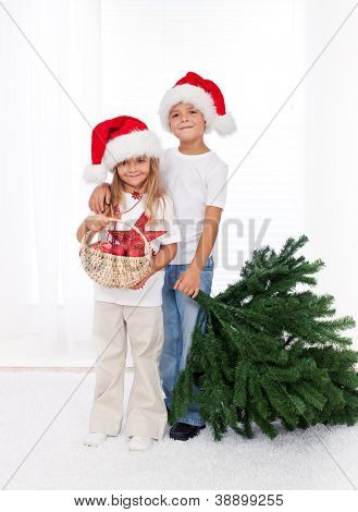 Kids wearing santa hats preparing to decorate the christmas tree - getting the props together