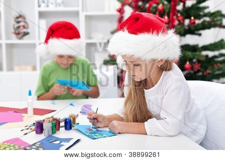 Kids making christmas or seasonal greeting cards