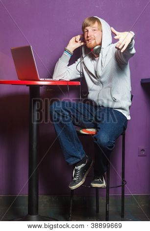 Cool young man with hoodie sitting working on laptop in cool location