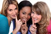 Three woman making shush gesture
