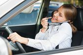 frivolous woman driving the car, painting her lips and talking on the phone