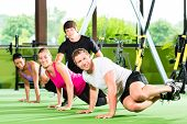 Group of people exercising with suspension trainer in fitness club or gym