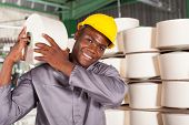 foto of raw materials  - textile factory worker carrying raw material on his shoulder - JPG