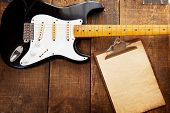 stock photo of wood pieces  - Vintage black double cutaway guitar on old wood surface and old clipboard - JPG