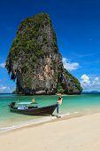 Постер, плакат: Длинный хвост лодки на тропическом пляже с известняковые скалы Паттайя Таиланд