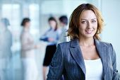 stock photo of foreground  - Image of pretty businesswoman looking at camera - JPG