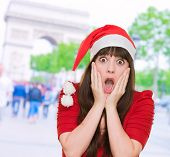 foto of horrifying  - scared woman wearing a christmas hat against a street background - JPG