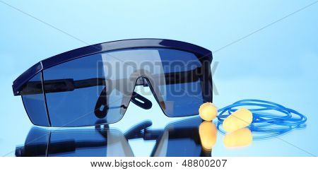 Eyeglasses tools and earplugs on blue background