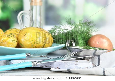 Batatas cozidas no cilindro na placa de madeira perto de guardanapo na mesa de madeira no fundo da janela