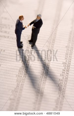 Financial Newspaper With Businessmen Figurines
