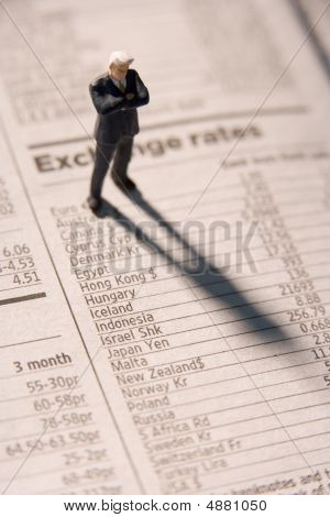 Financial Newspaper With Businessman Figurine