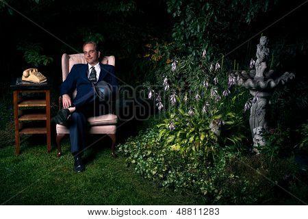 Man In Suit Sitting On Chair In Lush Garden