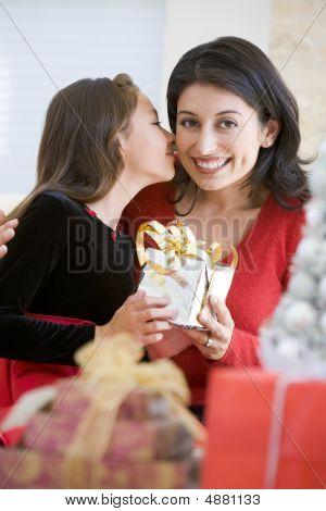 Mädchen, die überraschend ihre Mutter mit Weihnachtsgeschenk