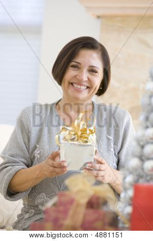 Woman Sitting On Sofa Holding A Christmas Gift