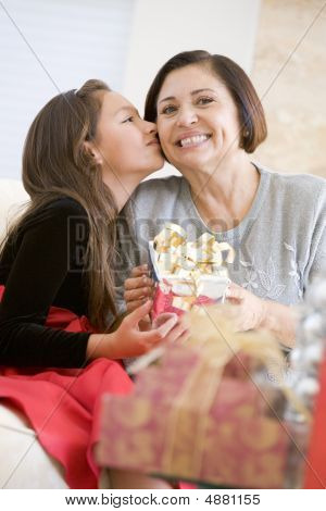 Granddaughter Kissing Grandmother On The Cheek,and Giving Her A Christmas Gift
