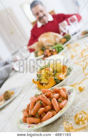 Dinner Table With Christmas Dishes,with Man In Background Carving Turkey