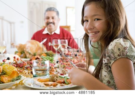 Grandfather And Granddaughter Sitting Down For Christmas Dinner
