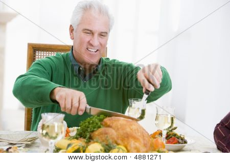 Man Carving Up Turkey At Christmas Dinner