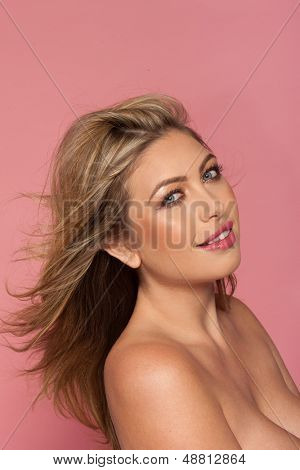 Portrait of a beautiful topless woman with her long blond hair blowing back off her face looking sideways at the camera, studio portrait on pink