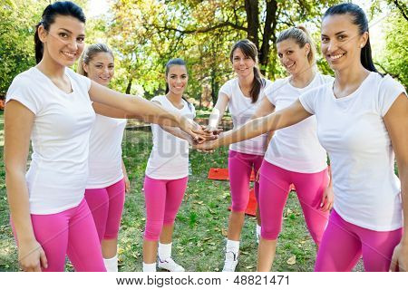 Sportswomen with hands together in huddle, agreement for fitness,