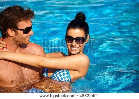 Pareja joven atractiva refrescante en la piscina al aire libre en verano, sonriendo.