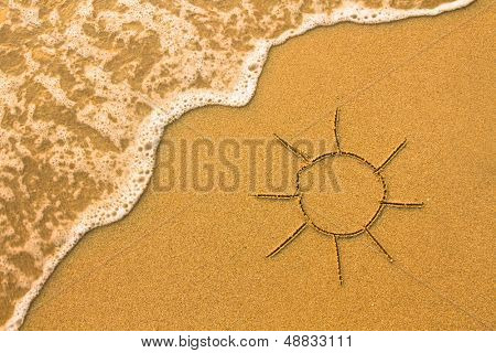 Sun drawn in the sand of a beach.