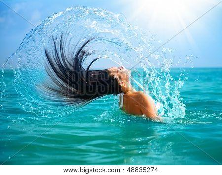 Beauty Model Girl Splashing Water with her Hair in the ocean. Beautiful Woman in Water